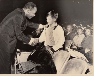 Boy shaking MLK's hand